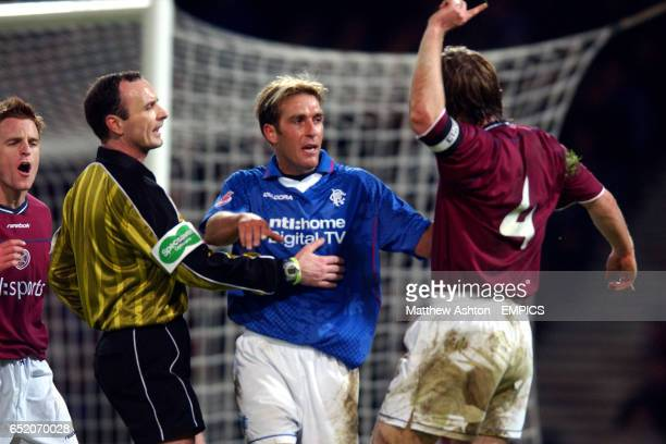 Referee Michael McCurry holds back Fernando Ricksen from Heart Of Midlothian's Steven Pressley