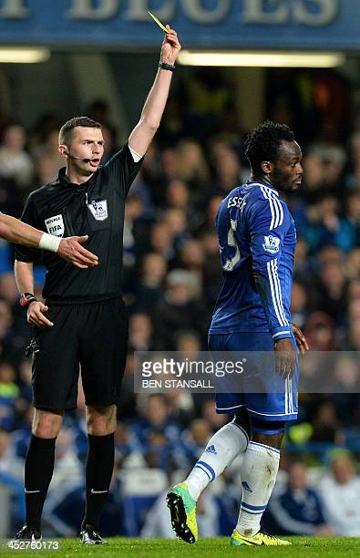 Referee Michael Oliver gives Chelsea's Ghanian midfielder Michael Essien a yellow card following a dive during the English Premier League football...