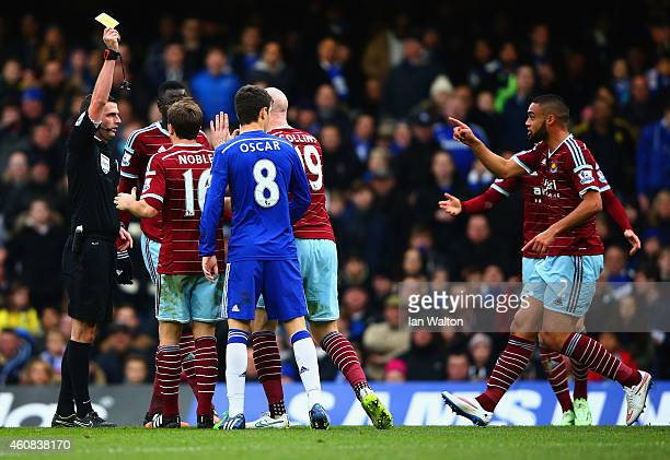Referee Michael Oliver showa James Collins of West Ham a yellow card during the Barclays Premier League match between Chelsea and West Ham United at...