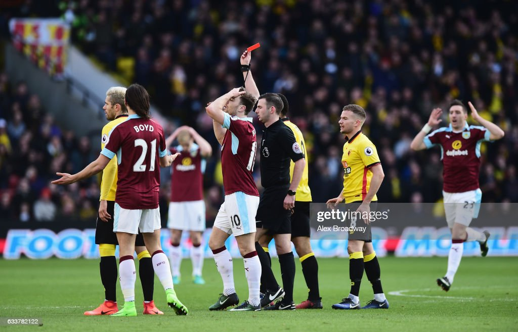 Referee Michael Oliver (C) shows a red card to Jeff Hendrick of Burnley (not pictured) during the Premier League match between Watford and Burnley at Vicarage Road on February 4, 2017 in Watford, England.