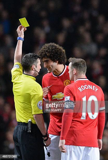 Referee Michael Oliver shows a yellow card to Manchester United's Belgian midfielder Marouane Fellaini during the FA Cup quarterfinal football match...