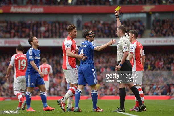 Referee Michael Oliver shows Chelsea's Cesc Fabregas a yellow card for diving in the penalty area