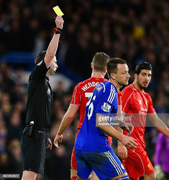 Referee Michael Oliver shows John Terry of Chelsea a yellow card during the Capital One Cup SemiFinal match between Chelsea and Liverpool at Stamford...