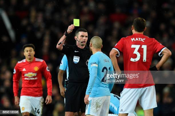 Referee Michael Oliver shows Manchester City's Spanish midfielder David Silva a yellow card during the English Premier League football match between...