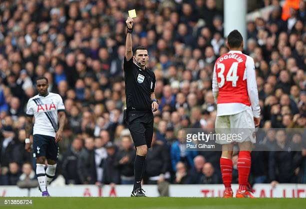 Referee Michael Oliver shows yellow card to Francis Coquelin of Arsenal during the Barclays Premier League match between Tottenham Hotspur and...