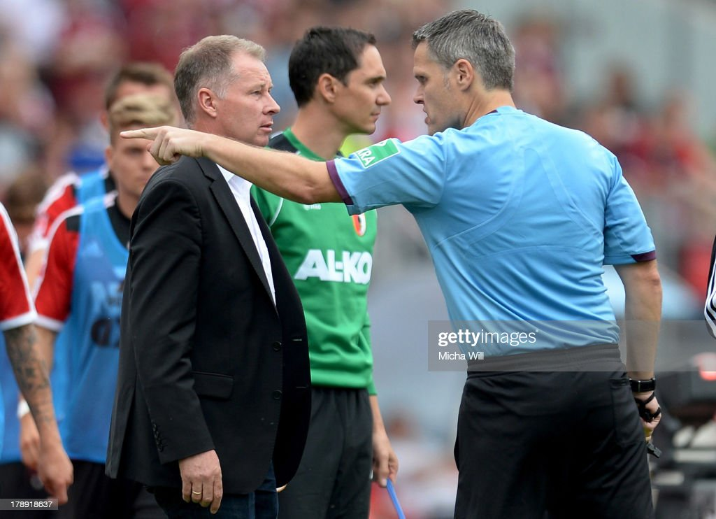 Referee Michael Weiner has words with CEO Stefan Reuter of Augsburg during the Bundesliga match between 1 FC Nuernberg and FC Augsburg at Grundig...