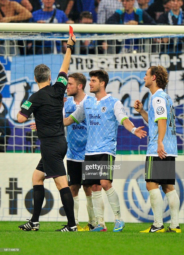 Referee Michael Weiner (L) shows Dominik Stahl (2nd L) of 1860 Muenchen the red card during the DFB Cup match between TSV 1860 Muenchen and Borussia Dortmund at Allianz Arena on September 24, 2013 in Munich, Germany.