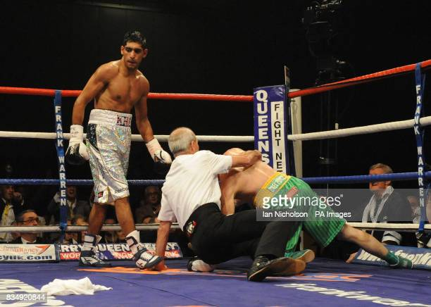 Referee Mickie Vann dives in to save Irishman Oisin Fagan in the second round after being beaten by Great Britain's Amir Khan in the lightweight bout...