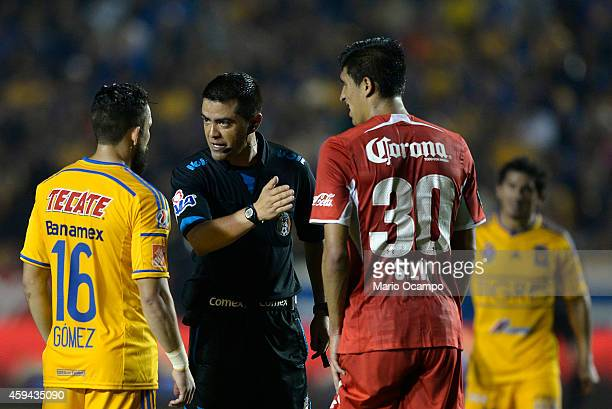 Referee Miguel Angel Ayala talks to Herculez Gomez of Tigres and Jesus Silva of Toluca during a match between Tigres UANL and Toluca as part of 17th...