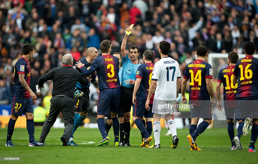 Referee Miguel Perez (C) pulls a red card for goalkeeper <a gi-track='captionPersonalityLinkClicked' href=/galleries/search?phrase=Victor+Valdes&family=editorial&specificpeople=552392 ng-click='$event.stopPropagation()'>Victor Valdes</a> (L) of Barcelona, held back by teammates, after the final whistle of the la Liga match between Real Madrid CF and FC Barcelona at Estadio Santiago Bernabeu on March 2, 2013 in Madrid, Spain.