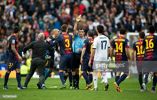 Referee Miguel Perez pulls a red card for goalkeeper Victor Valdes of Barcelona held back by teammates after the final whistle of the la Liga match...