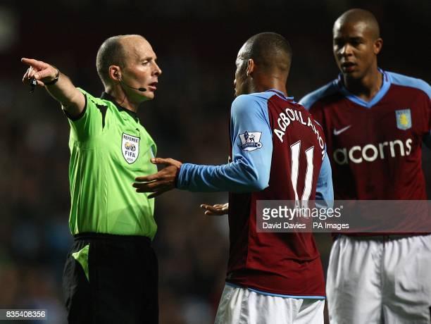 Referee Mike Dean and Aston Villa's Gabriel Agbonlahor argue