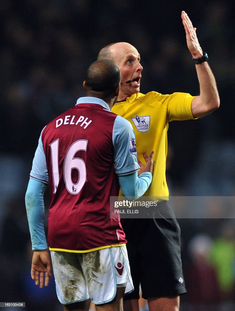 Referee Mike Dean gestures after a hand ball by Aston Villa's English midfielder Fabian Delph during the English Premier League football match between Aston Villa and Manchester City at Villa Park in Birmingham, central England, on March 4, 2013. Manchester City won the match 1-0. AFP PHOTO/Paul Ellis