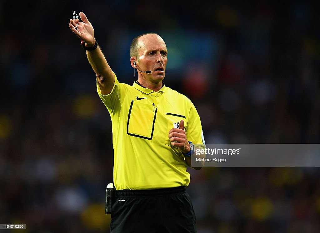Referee Mike Dean gestures during the Barclays Premier League match between Aston Villa and Manchester United on August 14, 2015 in Birmingham, United Kingdom.