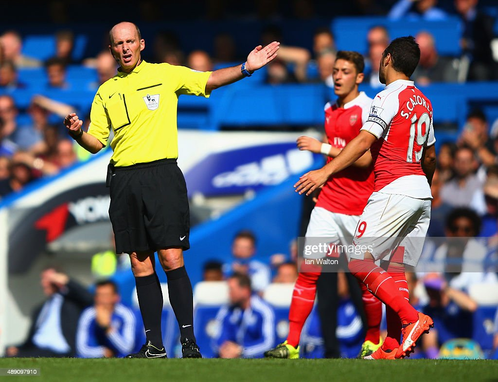 Referee Mike Dean gestures during the Barclays Premier League match between Chelsea and Arsenal at Stamford Bridge on September 19, 2015 in London, United Kingdom.