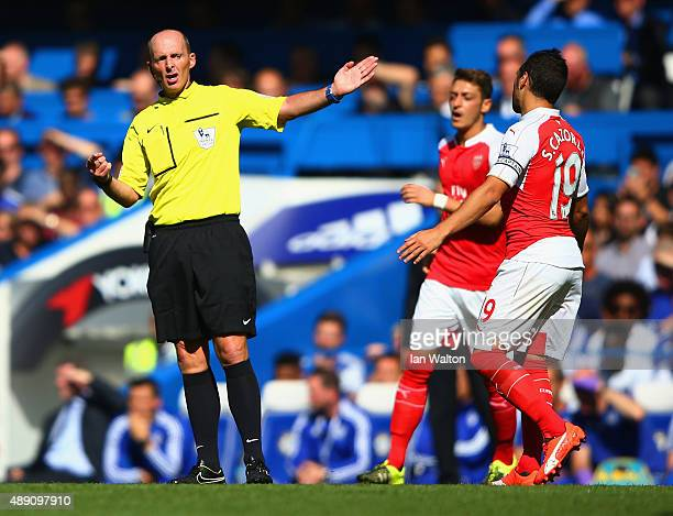 Referee Mike Dean gestures during the Barclays Premier League match between Chelsea and Arsenal at Stamford Bridge on September 19 2015 in London...