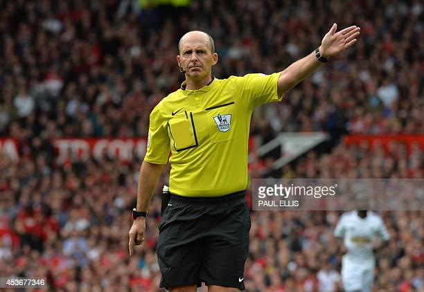 Referee Mike Dean gestures during the English Premier League football match between Manchester United and Swansea City at Old Trafford in Manchester...