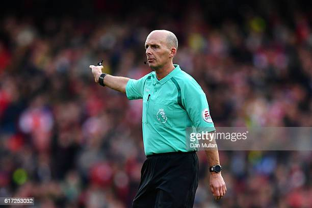 Referee Mike Dean gestures during the Premier League match between Arsenal and Middlesbrough at Emirates Stadium on October 22 2016 in London England