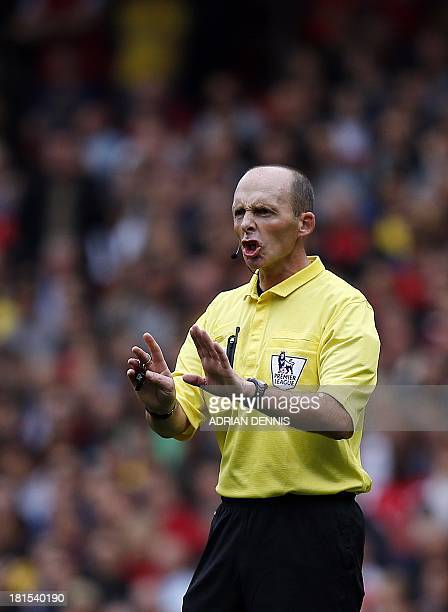 Referee Mike Dean gestures to the players during the English Premier League football match between Arsenal and Stoke City at the Emirates stadium in...