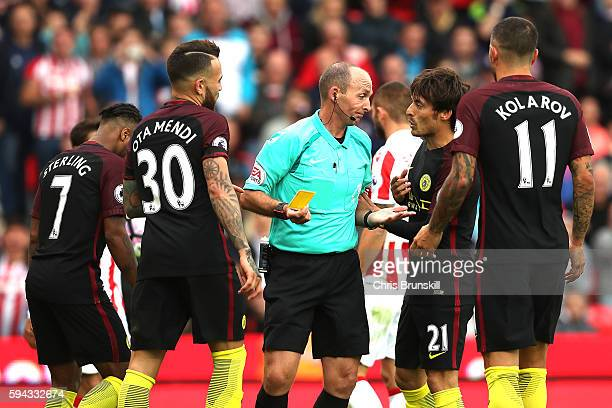 Referee Mike Dean is surrounded by Manchester City players after awarding a penalty during the Premier League match between Stoke City and Manchester...