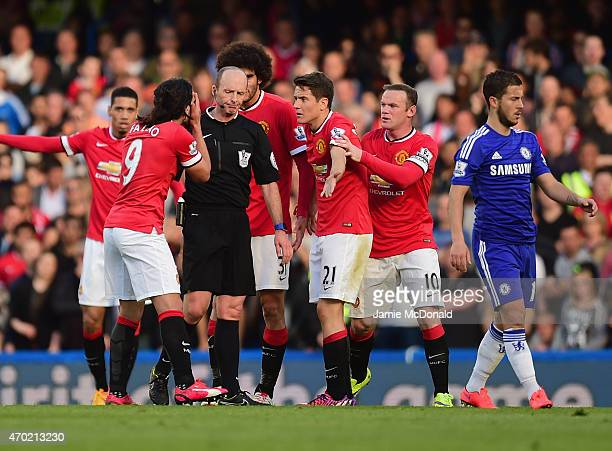 Referee Mike Dean is surrounded by Radamel Falcao García Marouane Fellaini Ander Herrera and Wayne Rooney of Manchester United during the Barclays...