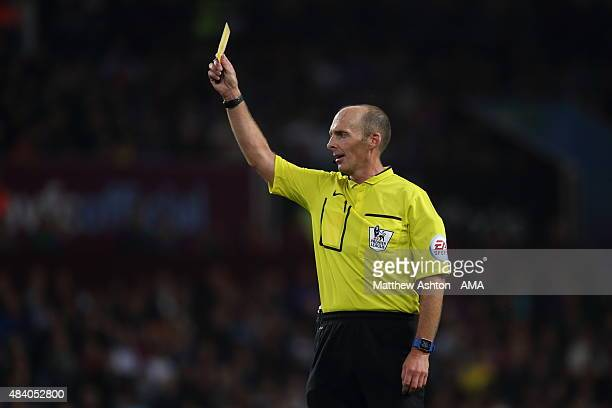 Referee Mike Dean issues a yellow card during the Barclays Premier League match between Aston Villa and Manchester United at Villa Park on August 14...