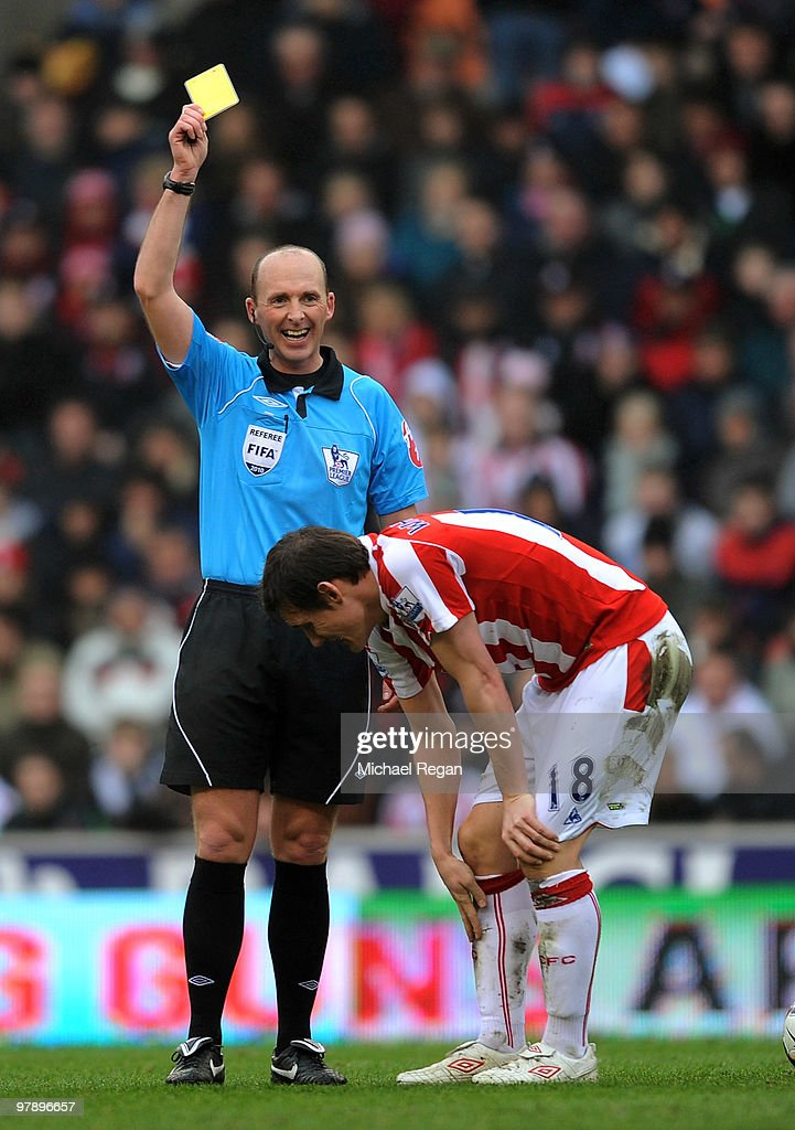 Referee Mike Dean laughs as he gives <a gi-track='captionPersonalityLinkClicked' href=/galleries/search?phrase=Dean+Whitehead&family=editorial&specificpeople=185232 ng-click='$event.stopPropagation()'>Dean Whitehead</a> of Stoke his first yellow card in the first half of the Barclays Premiership match between Stoke City and Tottenham Hotspur at the Britannia Stadium on March 20, 2010 in Stoke on Trent, England.