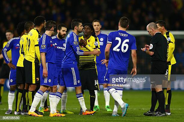 Referee Mike Dean prepares to show the yellow card to Diego Costa of Chelsea during the Barclays Premier League match between Watford and Chelsea at...