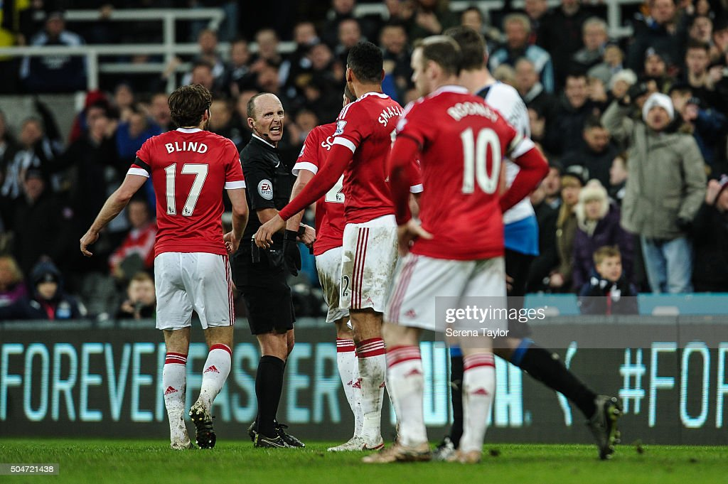 Referee Mike Dean (second from left) reacts as Manchester player surround him during the Barclays Premier League match between Newcastle United and Manchester United at St.James' Park on January 12, 2016, in Newcastle upon Tyne, England.