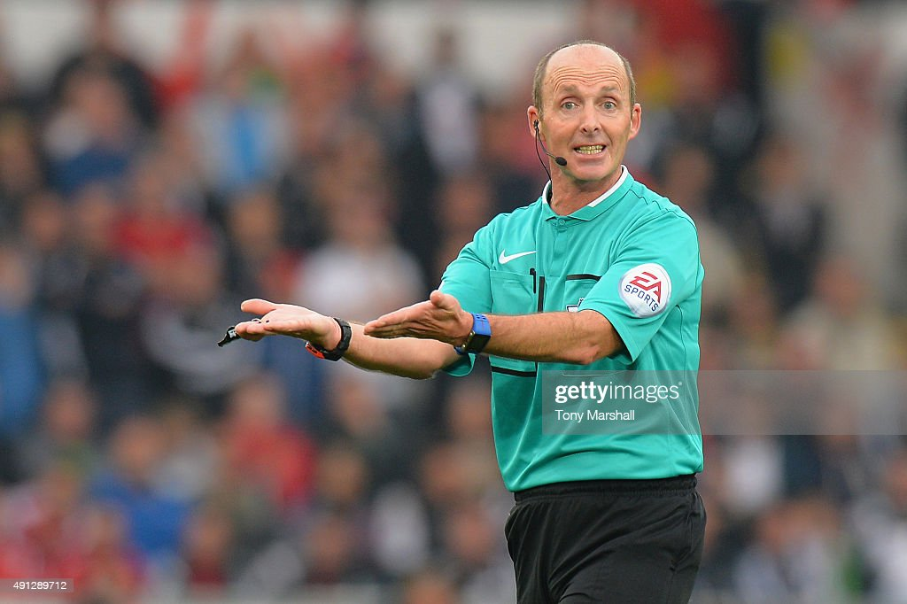 Referee Mike Dean reacts during the Barclays Premier League match between Swansea City and Tottenham Hotspur at Liberty Stadium on October 4, 2015 in Swansea, Wales.