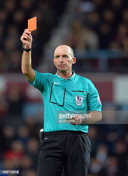 Referee Mike Dean shows a red card to Newcastle United's French midfielder Moussa Sissoko during the English Premier League football match between...