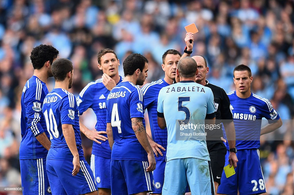 Referee Mike Dean shows a red card to Pablo Zabaleta of Manchester City during the Barclays Premier League match between Manchester City and Chelsea at the Etihad Stadium on September 21, 2014 in Manchester, England.