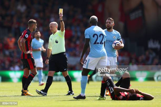 Referee Mike Dean shows Benjamin Mendy of Manchester City a yellow card during the Premier League match between AFC Bournemouth and Manchester City...