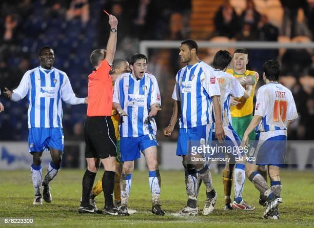 Referee Mike Dean shows Colchester United's Ian Henderson a red card