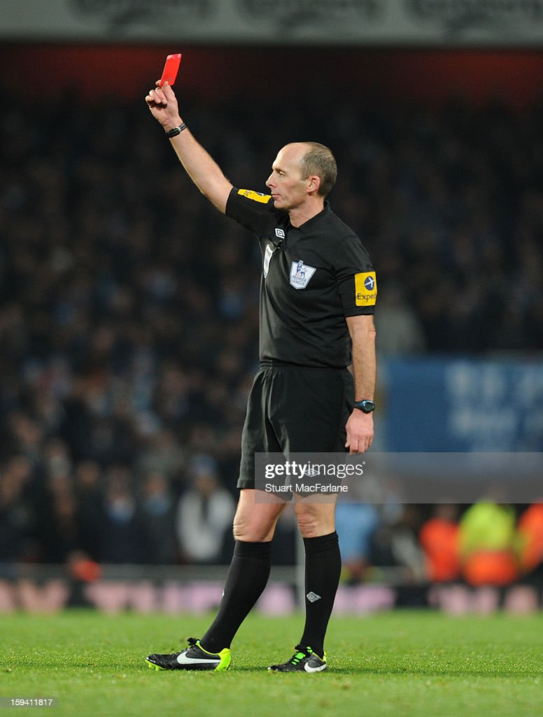Referee Mike Dean shows Man City captain Vincent Kompany a red card during the Barclays Premier League match between Arsenal and Manchester City at Emirates Stadium on January 13, 2013 in London, England.