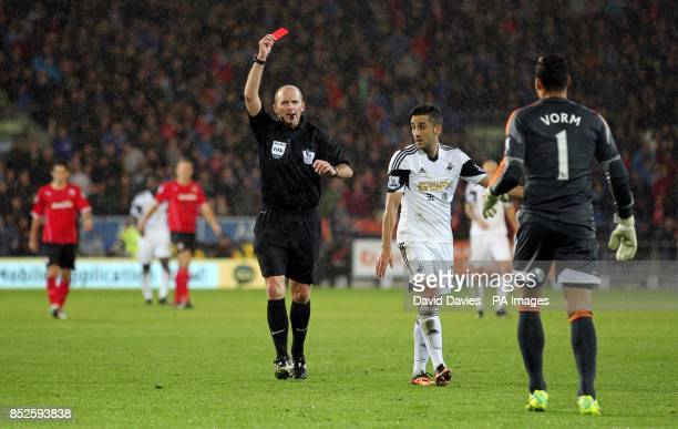 Referee Mike Dean shows Swansea City goalkeeper Michel Vorm the red card during the Barclays Premier League match at Cardiff City Stadium Cardiff