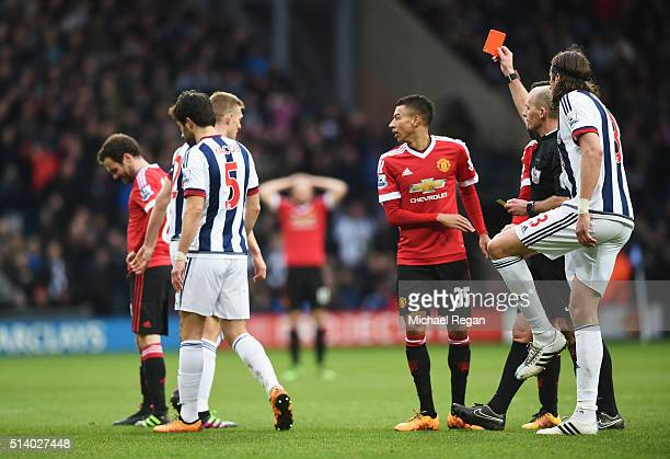 Referee Mike Dean shows the red card to Juan Mata of Manchester United during the Barclays Premier League match between West Bromwich Albion and...