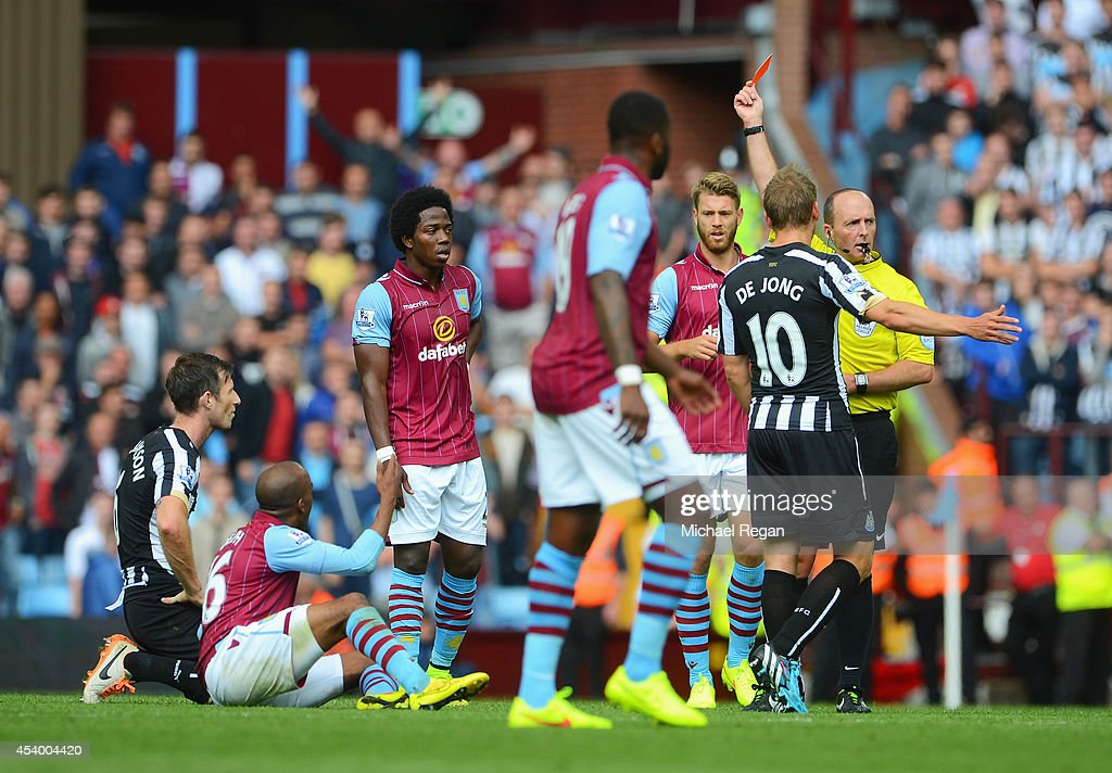 Referee Mike Dean shows the red card to Mike Williamson (L) of Newcastle United during the Barclays Premier League match between Aston Villa and Newcastle United at Villa Park on August 23, 2014 in Birmingham, England.