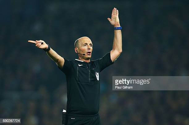 Referee Mike Dean signals during the Barclays Premier League match between West Ham United and Manchester United at the Boleyn Ground on May 10 2016...