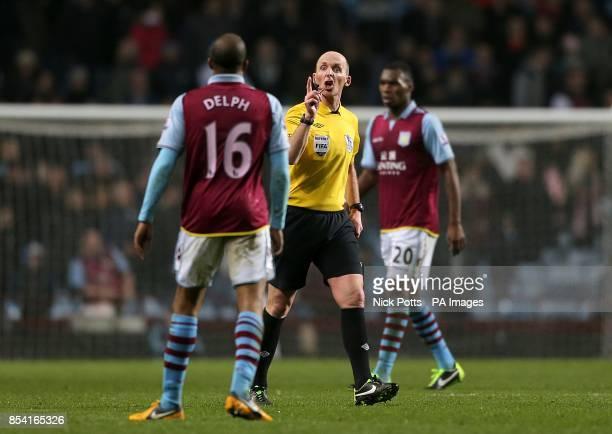 Referee Mike Dean speaks with Aston Villa's Fabian Delph as teammate Christian Benteke looks on