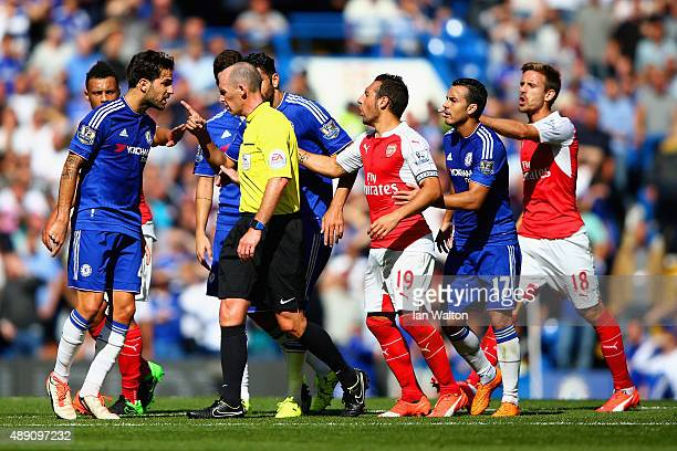 Referee Mike Dean talks with Cesc Fabregas of Chelsea during the Barclays Premier League match between Chelsea and Arsenal at Stamford Bridge on...