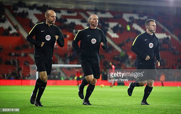 Referee Mike Dean warms up with his assistant referees prior to the Premier League match between Southampton and Tottenham Hotspur at St Mary's...