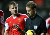Referee Mike Jones checks his bleeding nose after being accidentally hit in the face by Newcastle United's French midfielder Moussa Sissoko during...