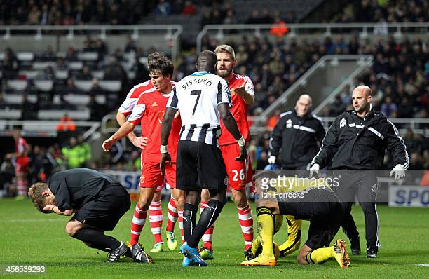 Referee Mike Jones is accidentally felled by a stray arm from Newcastle's Moussa Sissoko during the Barclays Premier League match between Newcastle...