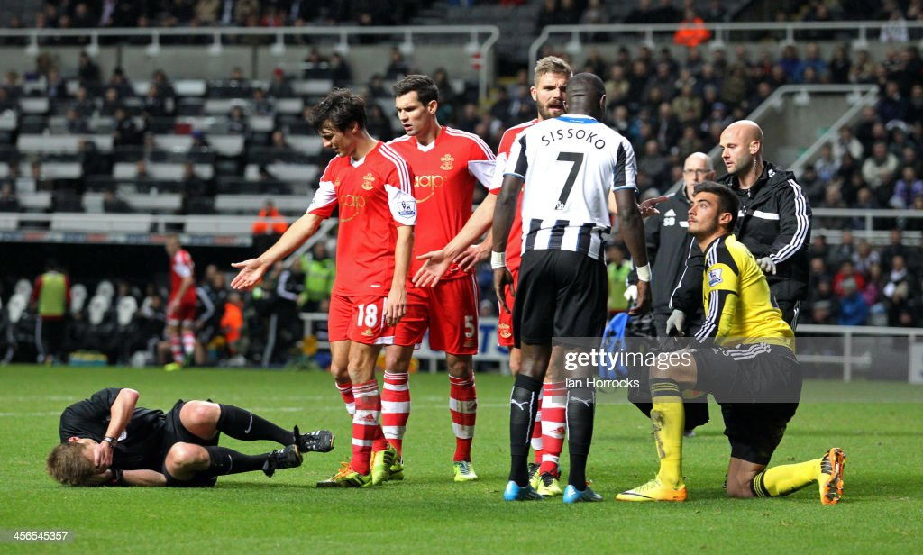 Referee Mike Jones is accidentally felled by a stray arm from Newcastle's Moussa Sissoko during the Barclays Premier League match between Newcastle United and Southampton at St James' Park on December 14, 2013 in Newcastle upon Tyne, England.