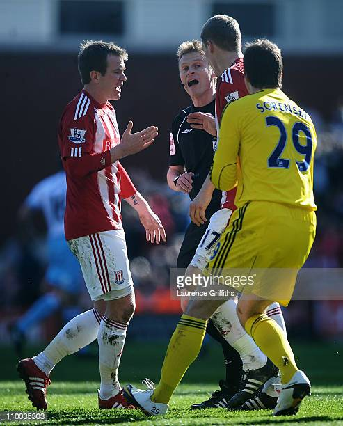 Referee Mike Jones is confronted by Glenn Whelan and goalkeeper Thomas Sorensen of Stoke City after allowing the opening West Ham United goal during...
