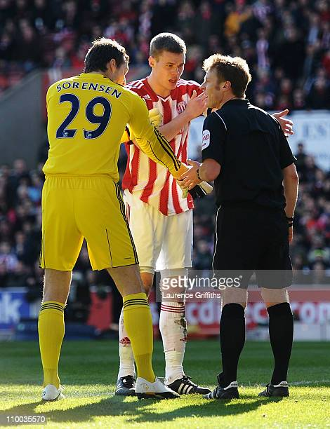 Referee Mike Jones is confronted by Ryan Shawcross of Stoke City and goalkeeper Thomas Sorensen of Stoke City after allowing the opening West Ham...