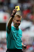 Referee Mike Jones issues a yellow card during the Barclays Premier League match between Swansea City and Newcastle United at Liberty Stadium on...