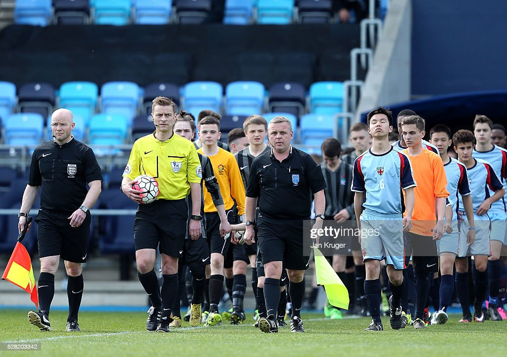 Referee Mike Jones leads the teams out during the under 16 Schools' Cup final match between Thomas Telford School and Samuel Whitbread Academy at the Academy Training Ground on May 04, 2016 in Manchester, England.