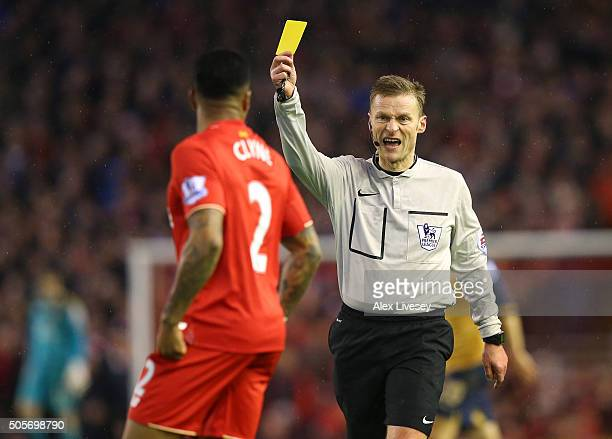 Referee Mike Jones shows a yellow card during the Barclays Premier League match between Liverpool and Arsenal at Anfield on December 13 2016 in...